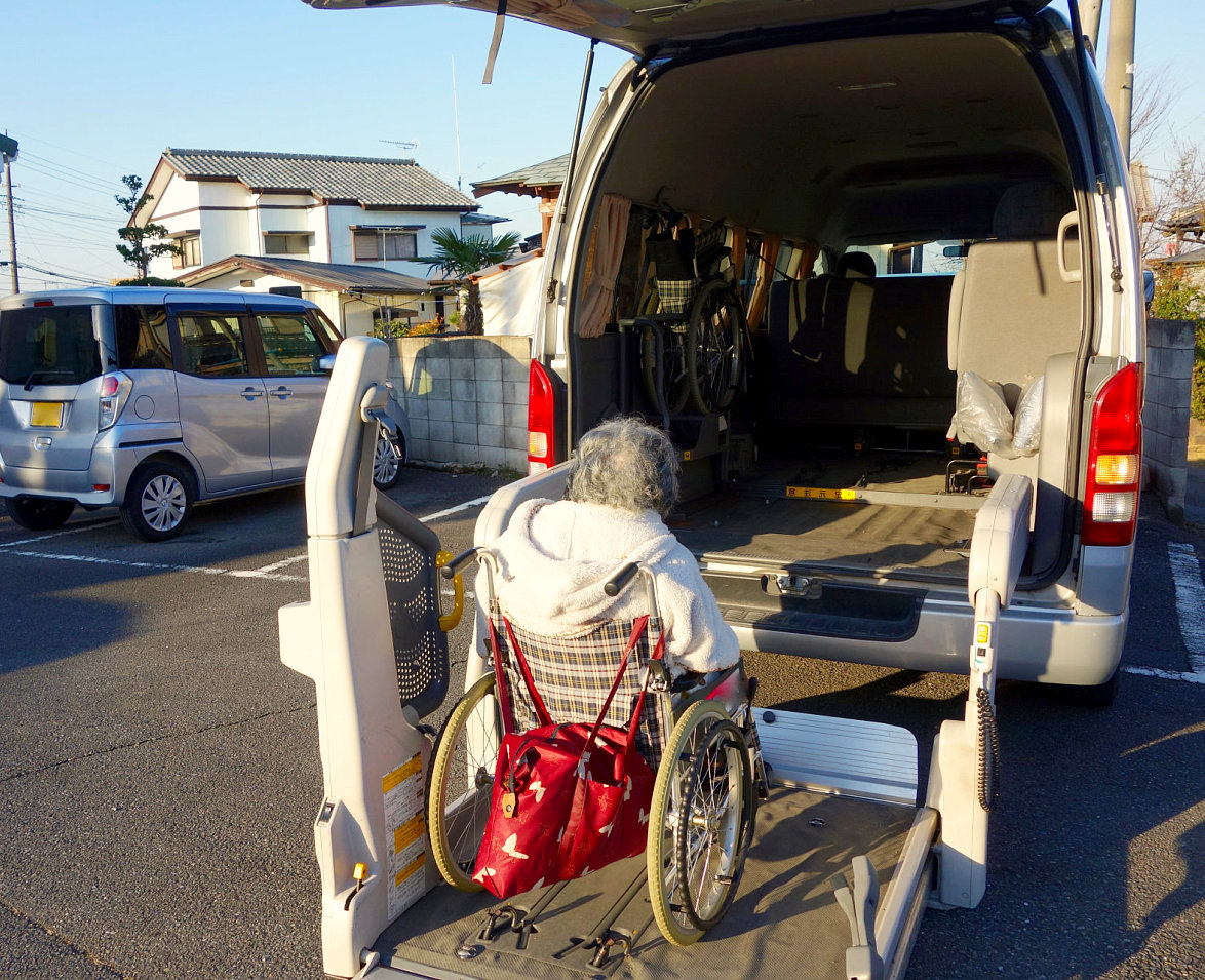 elderly woman rides on van by the help of wheelchair lifts