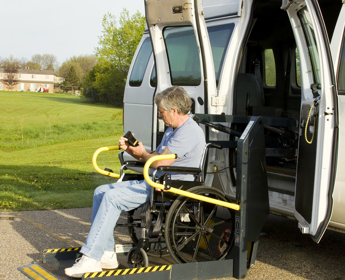 senior man on wheelchair exits van using wheelchair lifts and ramps