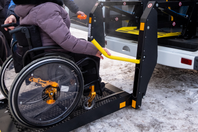 senior woman on wheelchair rides on van using wheelchair lifts