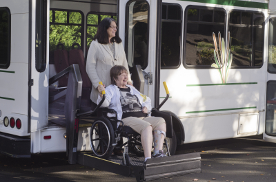 senior woman on wheelchair helped off by van using chair lift