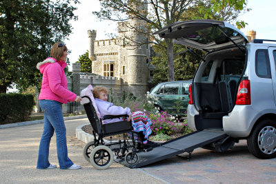 woman assisting senior woman on wheelchair to ride on vehicle for her rehabilitation appointment